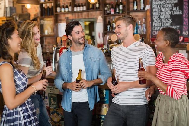 Amigos sosteniendo botellas de cerveza en el pub