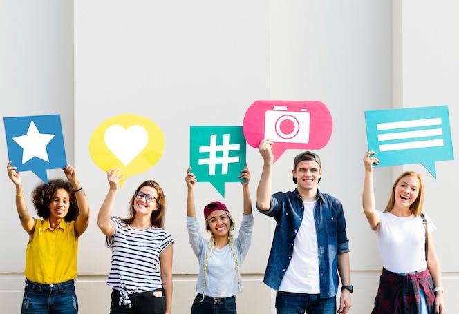 Amigos sosteniendo burbujas de pensamiento con iconos de concepto de redes sociales