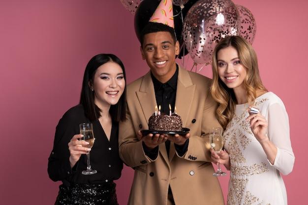 Amigos sosteniendo un pastel de cumpleaños