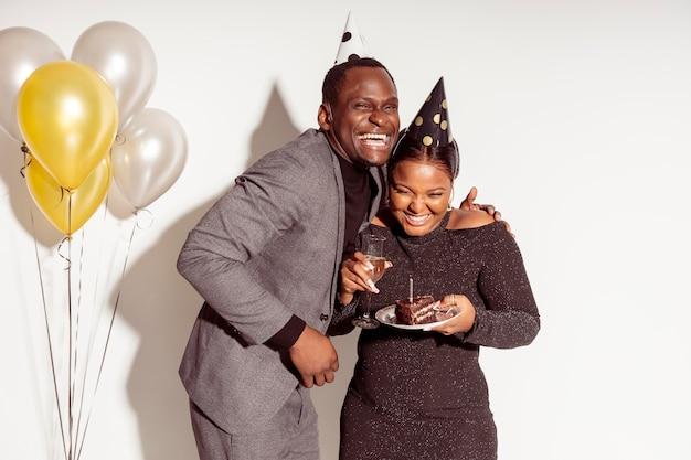 Amigos sosteniendo pastel y risa feliz cumpleaños