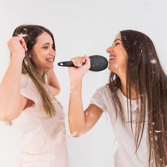 Amigos sosteniendo peine cantando canción con sus amigos bailando