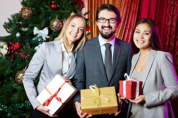 Amigos sosteniendo regalos con el abeto de fondo