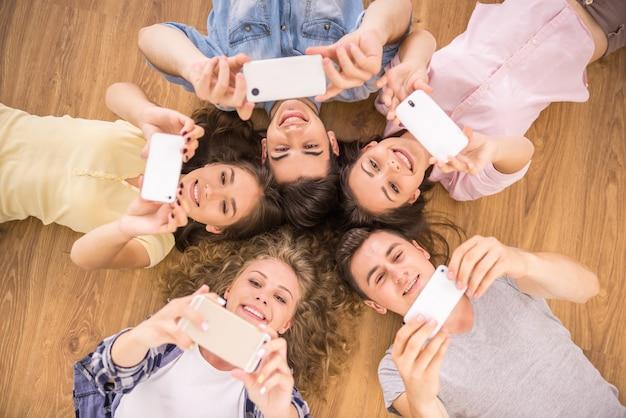 Amigos con teléfonos inteligentes acostado en el piso en círculo.