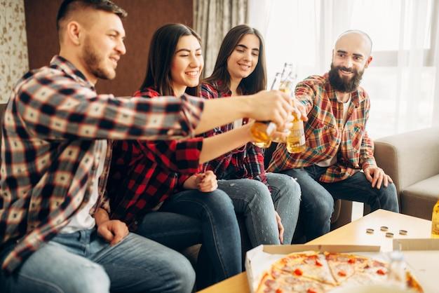 Amigos tintinean botellas con cerveza en la fiesta en casa