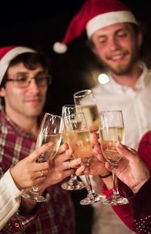 Amigos tintinean copas de champán tostado de navidad