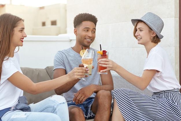 Amigos tintineando copas de vino y cócteles celebrando una ocasión especial