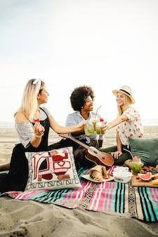 Amigos tintineando sus bebidas en una fiesta en la playa