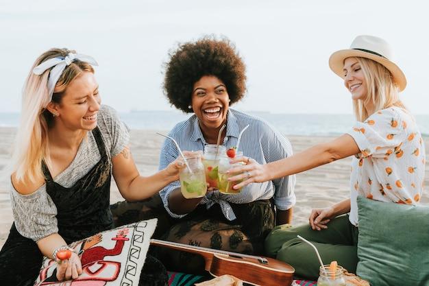 Amigos tintineando sus copas en una fiesta en la playa