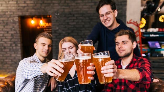 Amigos tintineando vasos con cerveza en pub