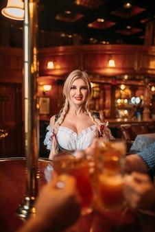 Amigos tintineo de tazas en el bar de cerveza, camarera en el mostrador