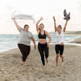 Amigos de tiro completo corriendo en la playa