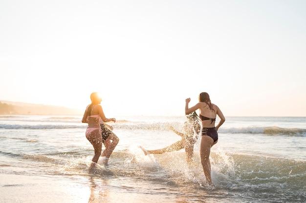 Amigos de tiro completo divirtiéndose en la orilla