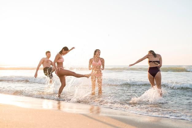Amigos de tiro completo divirtiéndose en la playa