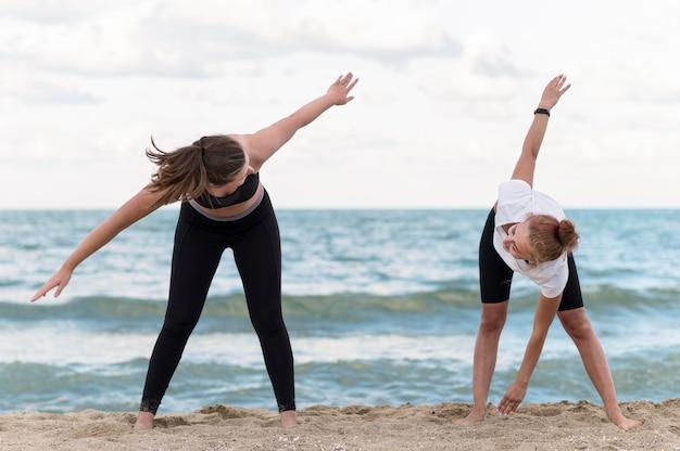 Amigos de tiro completo haciendo ejercicio en la playa