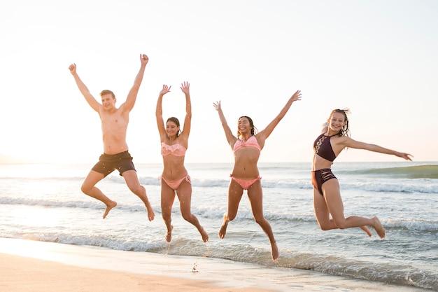 Amigos de tiro completo saltando en la orilla