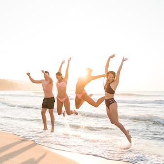 Amigos de tiro completo saltando en la playa