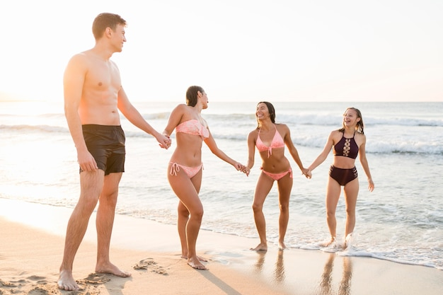 Amigos de tiro completo tomados de la mano en la playa