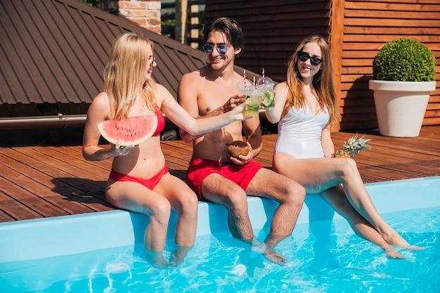 Amigos de tiro largo disfrutando de cócteles en la piscina
