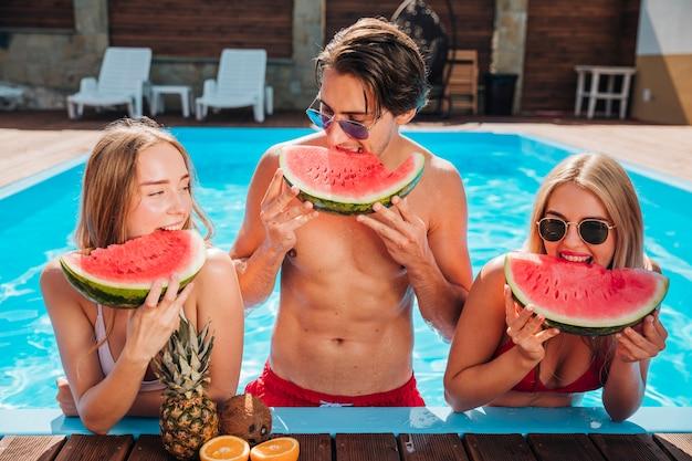 Amigos de tiro medio comiendo sandía en la piscina