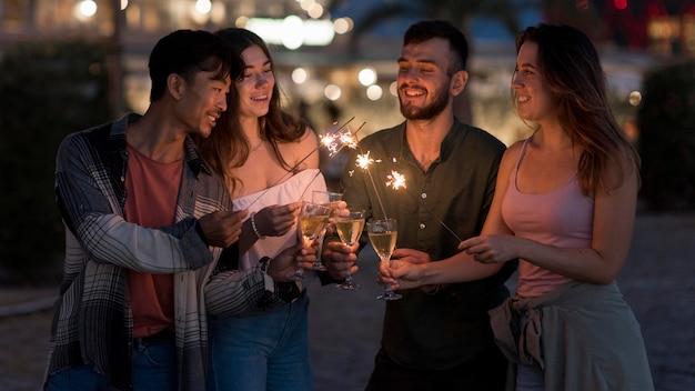 Amigos de tiro medio con fuegos artificiales en la noche