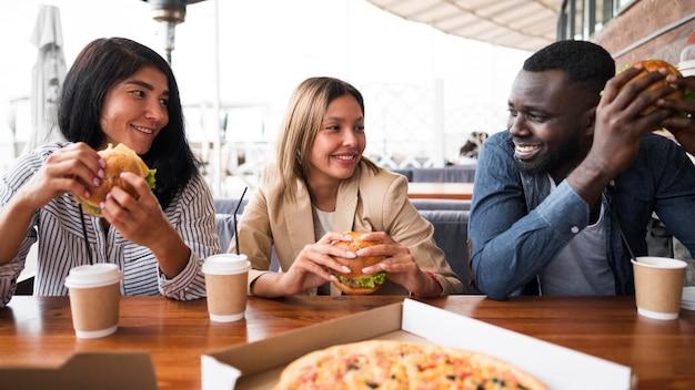 Amigos de tiro medio en la mesa con hamburguesas