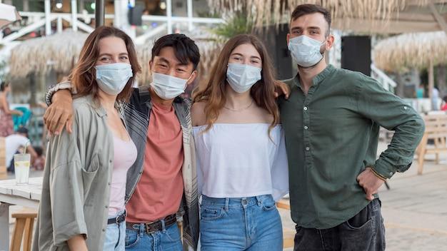 Amigos de tiro medio posando con máscaras