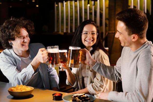 Amigos de tiro medio sosteniendo jarras de cerveza