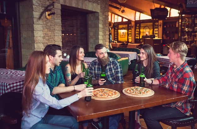 Amigos tomando bebidas y comiendo pizzas en un bar.