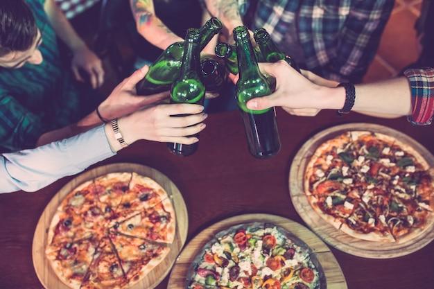 Amigos tomando una copa en un bar y comiendo pizzas