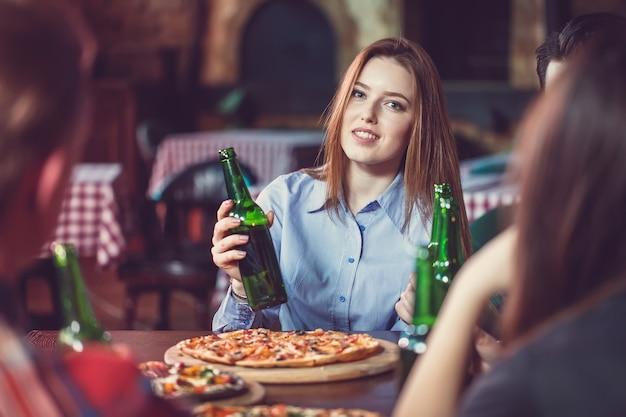 Amigos tomando una copa en un bar, están sentados en una mesa de madera con cervezas y pizza. concéntrese en una hermosa niña tocando su botella.