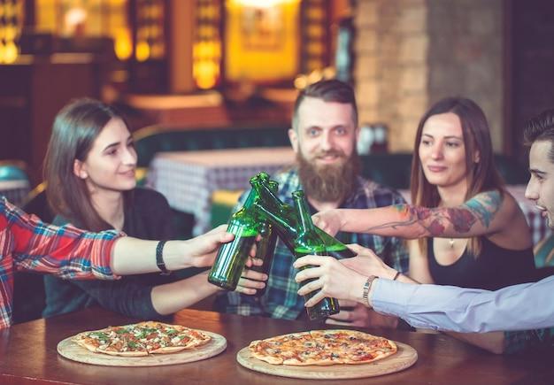 Amigos tomando una copa en un bar, están sentados en una mesa de madera con cervezas y pizza.