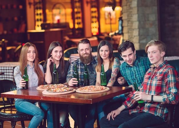 Amigos tomando una copa en un bar, sentado en una mesa de madera con cervezas y pizzas.