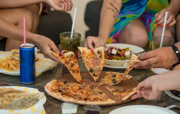 Amigos tomando rebanadas de pizza de la mesa.