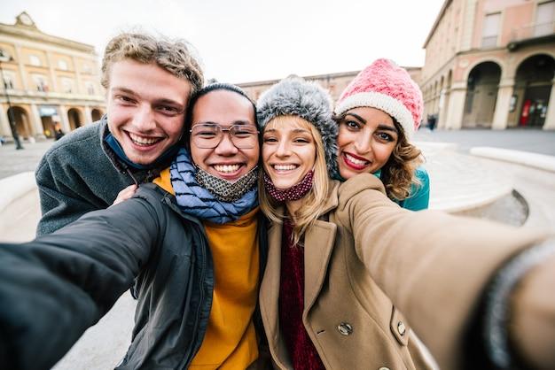 Amigos tomando un selfie afuera en la ciudad - nuevo concepto de estilo de vida normal con jóvenes divirtiéndose juntos en vacaciones con mascarilla facial.