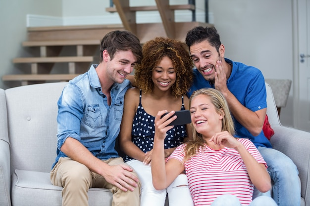 Amigos tomando selfie mientras está sentado en el sofá