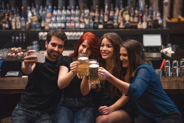 Amigos tomando un selfie en el mostrador de bar mediante teléfono móvil