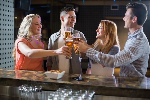 Amigos tostado vasos de cerveza en barra de bar