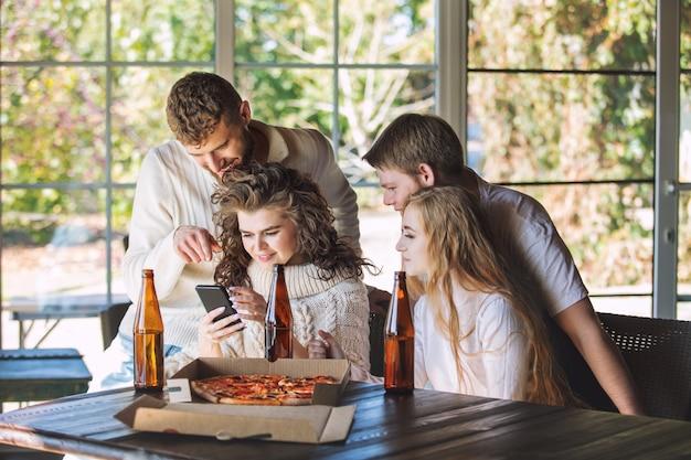 Amigos tres dos hombres y dos mujeres adultos jóvenes hermosos y felices junto con el móvil