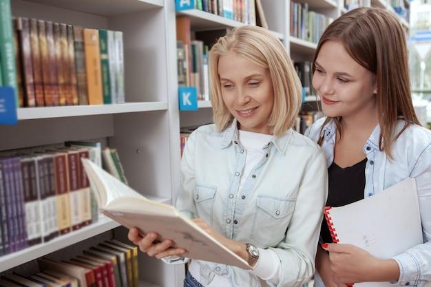 Amigos de la universidad en la biblioteca juntos