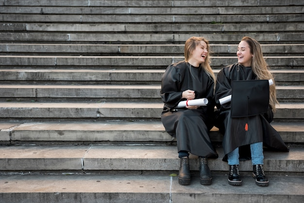 Amigos de la universidad de tiro largo riendo en las escaleras