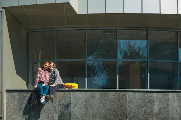 Los amigos de la universidad toman un descanso después de las clases abrazándose