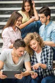 Amigos de la universidad viendo fotos en el teléfono en el descanso.