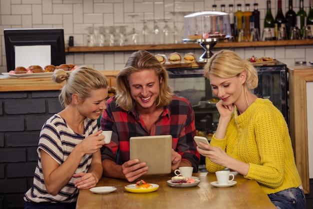 Amigos usando tableta digital y teléfono inteligente