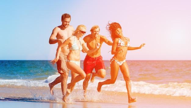 Amigos en vacaciones en la playa corriendo y jugando por el océano