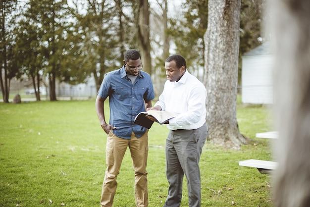 Amigos varones afroamericanos de pie en el parque y discutiendo la biblia