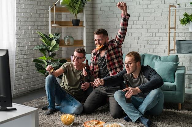 Amigos varones alegres viendo deportes en la televisión y comiendo pizza