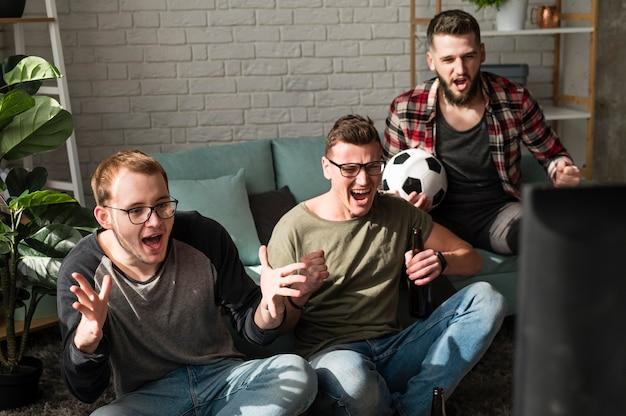 Amigos varones alegres viendo deportes en la televisión con fútbol