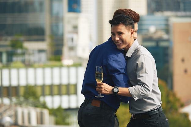 Amigos varones asiáticos abrazándose en la fiesta de champán en la azotea urbana