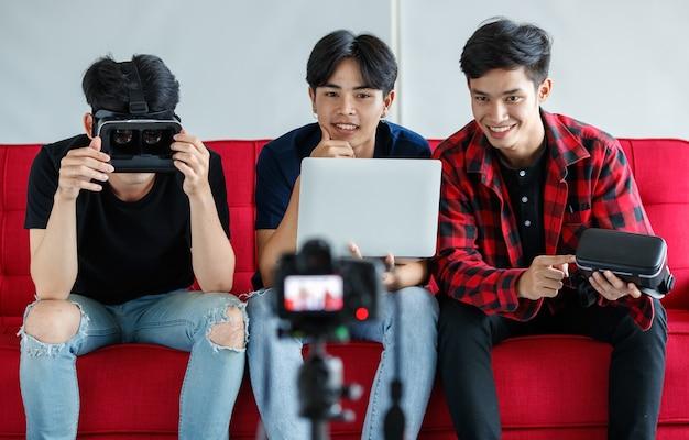 Amigos varones asiáticos con auriculares vr y una computadora portátil sentados en el sofá y grabando videos para el blog de tecnología en casa