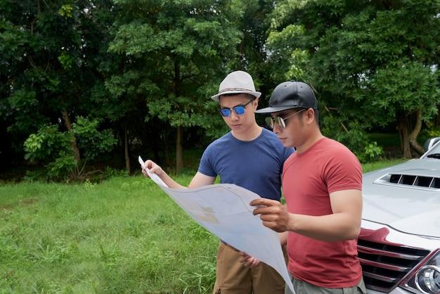 Amigos varones asiáticos de pie en coche en camino rural y mirando el mapa grande